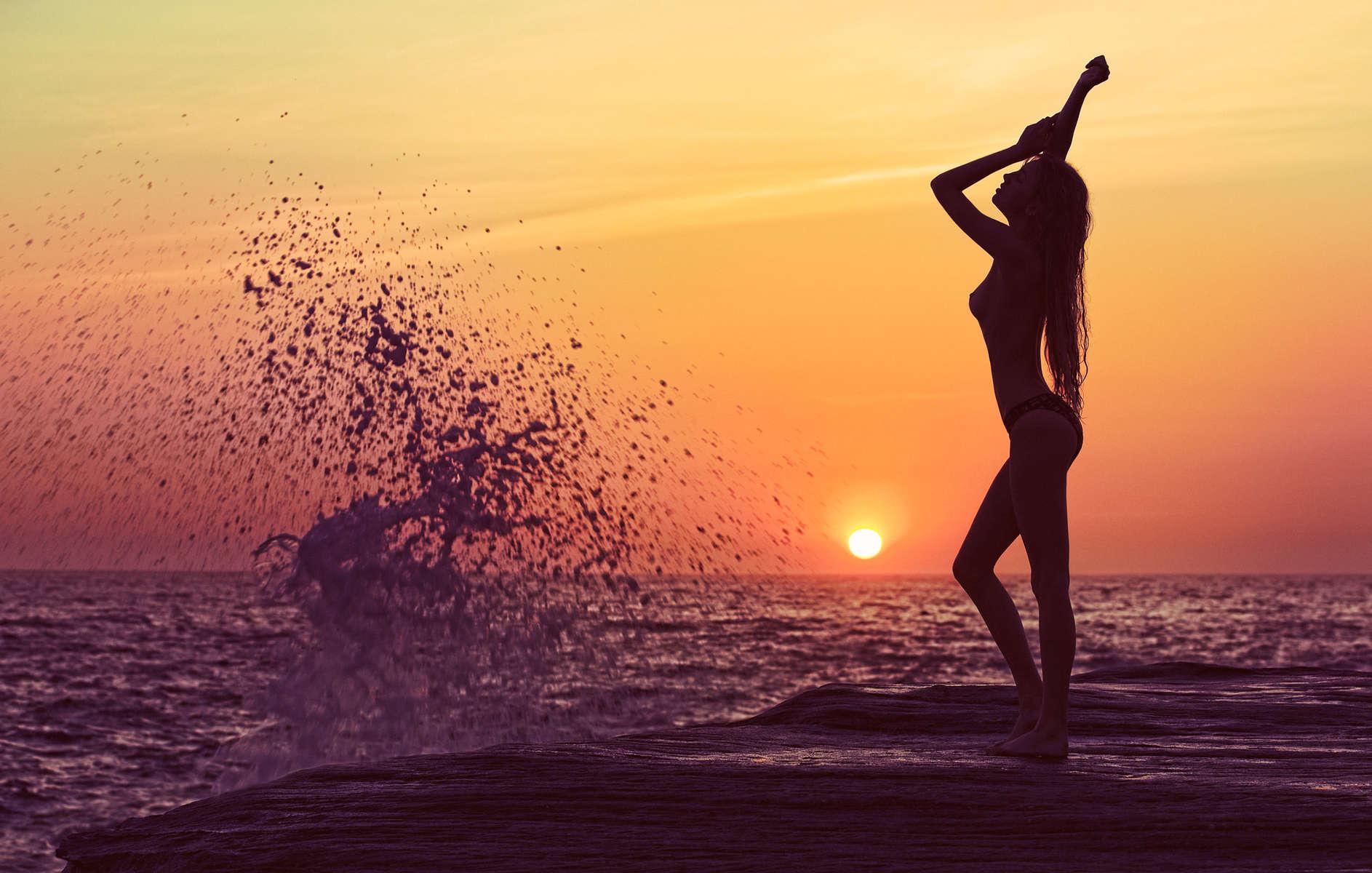 Девушка на закате на пляже со спины фото